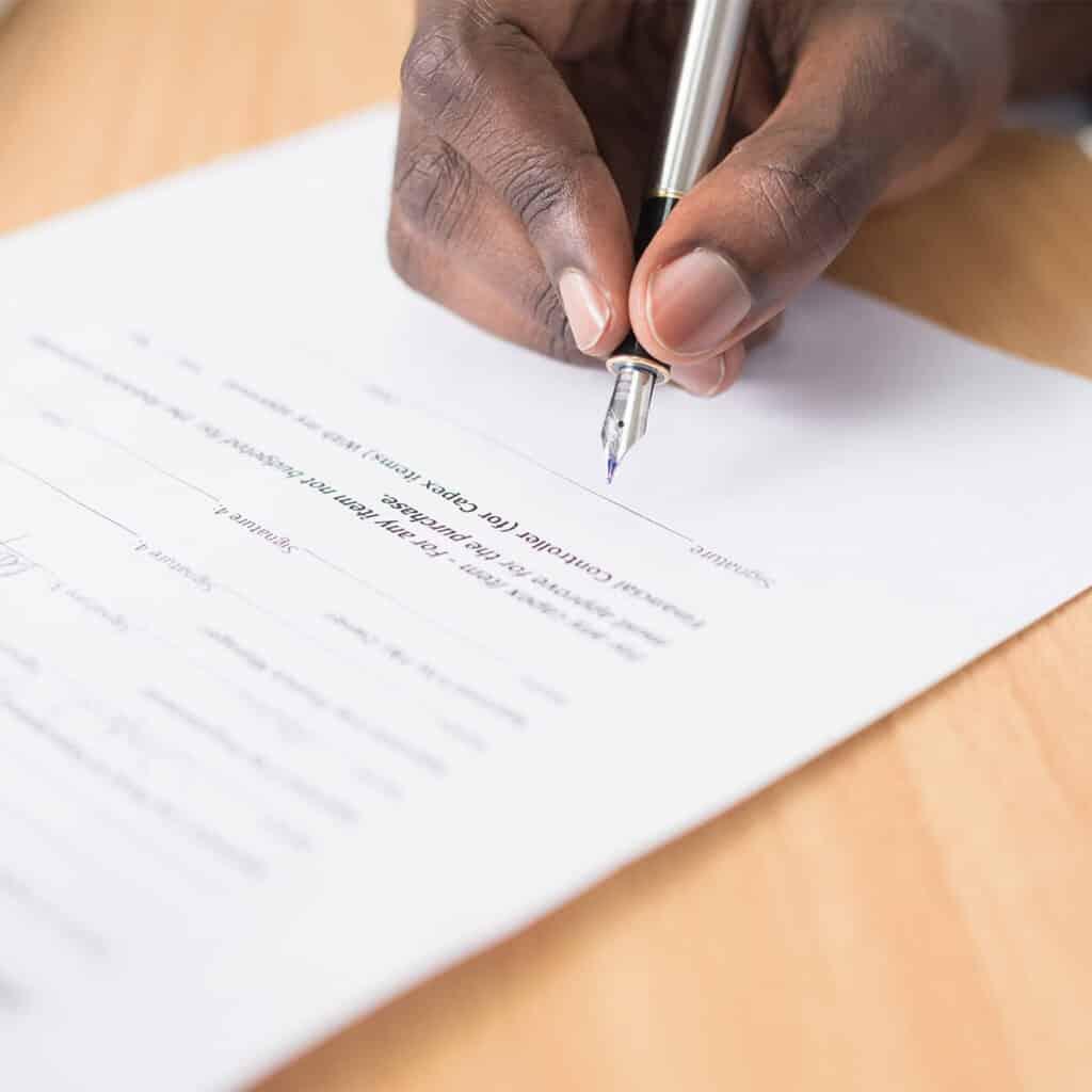 En person skriver på kontrakt relaterat till advokatbyrå tjänster